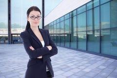 Bedrijfsvrouw die zich op straat tegen de moderne bureaubouw bevinden Royalty-vrije Stock Afbeeldingen