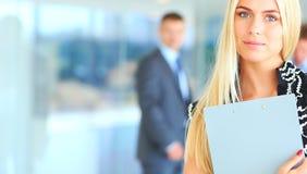 Bedrijfsvrouw die zich in voorgrond in bureau bevinden Royalty-vrije Stock Fotografie