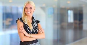 Bedrijfsvrouw die zich in voorgrond in bureau bevinden Stock Foto's