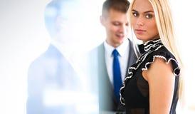 Bedrijfsvrouw die zich in voorgrond in bureau bevinden Royalty-vrije Stock Foto's