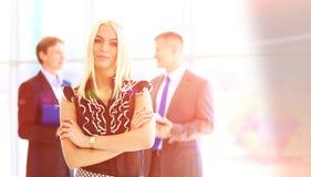 Bedrijfsvrouw die zich in voorgrond in bureau bevinden Royalty-vrije Stock Afbeelding