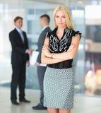 Bedrijfsvrouw die zich in voorgrond in bureau bevinden Royalty-vrije Stock Foto