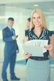 Bedrijfsvrouw die zich in voorgrond met een omslag in haar handen bevinden Royalty-vrije Stock Afbeelding