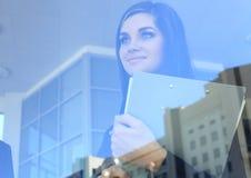 Bedrijfsvrouw die zich in voorgrond met een tablet bevinden Stock Afbeelding