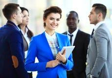 Bedrijfsvrouw die zich in voorgrond met een tablet in haar handen bevinden Stock Afbeeldingen