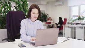 Bedrijfsvrouw in een blauw overhemd die aan laptop in bureau werken stock footage