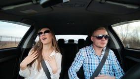 Bedrijfsvrouw en man die als gek dansen terwijl het drijven van auto na succes stock video
