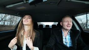 Bedrijfsvrouw en man die als gek dansen terwijl het drijven van auto na succes stock footage