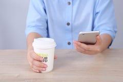 Bedrijfsvrouw gebruikend smartphone en houdend koffiekop in bureau Stock Fotografie