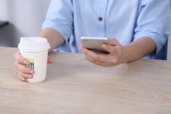 Bedrijfsvrouw gebruikend smartphone en houdend koffiekop in bureau Stock Afbeelding