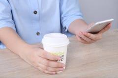Bedrijfsvrouw gebruikend smartphone en houdend koffiekop in bureau Royalty-vrije Stock Afbeeldingen