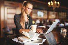 Bedrijfsvrouw in glazen binnen met koffie en laptop die nota's in restaurant nemen stock afbeelding