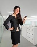 Bedrijfsvrouw in kostuum op celtelefoon op kantoor Stock Afbeeldingen
