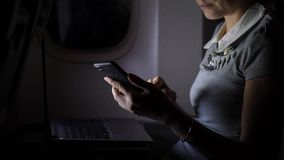 Bedrijfsvrouw in lijnvliegtuig het texting in smartphone bij nacht