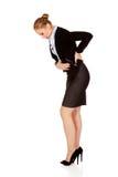 Bedrijfsvrouw met achterproblemen en maagpijn Stock Afbeelding