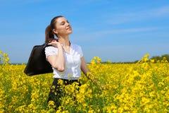 Bedrijfsvrouw met aktentas het ontspannen in de openlucht onderzon van het bloemgebied Jong meisje op geel raapzaadgebied Mooi de Royalty-vrije Stock Foto's