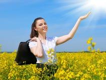 Bedrijfsvrouw met aktentas het ontspannen in de openlucht onderzon van het bloemgebied Jong meisje op geel raapzaadgebied Mooi de Royalty-vrije Stock Afbeelding