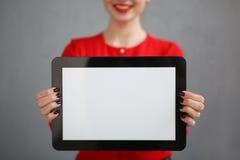 bedrijfsvrouw met een rood overhemd en een glazenportret, die een tablet in zijn handen houden Stock Fotografie