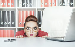 Bedrijfsvrouw met grote ogen die achter lijst verbergen stock foto