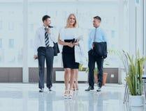 Bedrijfsvrouw met haar collega's die zich in de hal van het bureau bevinden Royalty-vrije Stock Afbeelding