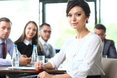 Bedrijfsvrouw met haar personeel, mensengroep op achtergrond stock fotografie