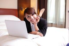 Bedrijfsvrouw met notitieboekje die in hotel liggen Stock Foto's