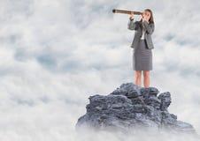 Bedrijfsvrouw met telescoop op bergpiek in de wolken Stock Fotografie