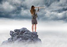 Bedrijfsvrouw met telescoop op bergpiek tegen onweerswolken Stock Afbeelding