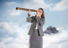 Bedrijfsvrouw met telescoop tegen bergpiek in de wolken Royalty-vrije Stock Foto's