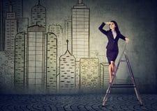 Bedrijfsvrouw op een ladder die ver weg het voorspellen onroerende goederenmarkt kijken stock foto