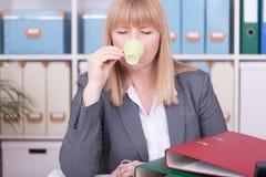 Bedrijfsvrouw op het kantoor die een kop van koffie drinken stock foto's