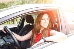 Bedrijfsvrouw in rode kledingszitting in auto Stock Afbeelding