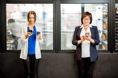 Bedrijfsvrouwen die telefoons in het bureau van de bakkerijopslag met behulp van royalty-vrije stock foto's