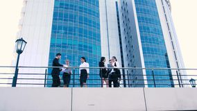 Bedrijfsvrouwen en bedrijfsmannen die op terras spreken Van onderaan schot stock video