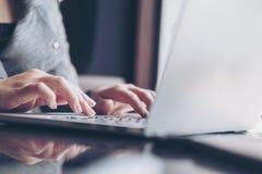 Bedrijfsvrouwen` s handen die en op laptop toetsenbord op glaslijst werken typen royalty-vrije stock fotografie