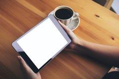 Bedrijfsvrouwen` s handen die zwarte tabletpc met lege witte het scherm en koffiekop op houten lijst op koffieachtergrond houden Royalty-vrije Stock Foto's