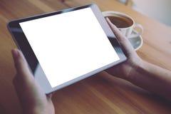 Bedrijfsvrouwen` s handen die zwarte tabletpc met lege witte het scherm en koffiekop op houten lijst op koffieachtergrond houden Stock Foto