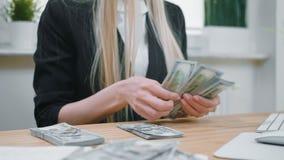 Bedrijfsvrouwen tellend contant geld in handen Gewassenmening van wijfje in elegante kostuumzitting bij houten bureau en groot te stock video
