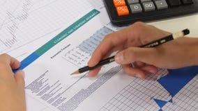 Bedrijfsvrouwenanalyse van financiële verslagen stock footage