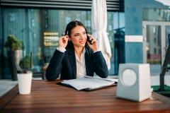 Bedrijfsvrouwenbesprekingen door mobiele telefoon in koffie royalty-vrije stock foto's