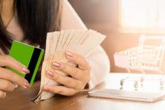 Bedrijfsvrouwenhand die geld ter beschikking voor betaling van creditcardvorm het winkelen online schuld voorbereiden stock foto