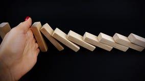 Bedrijfsvrouwenhand met rode spijkers die de domino's tegenhouden dalend op donkere achtergrond, bedrijfsconceptenbeeld Stock Afbeeldingen