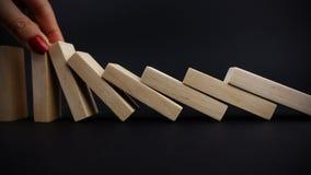 Bedrijfsvrouwenhand met rode spijkers die de domino's tegenhouden dalend op donkere achtergrond, bedrijfsconceptenbeeld Stock Fotografie