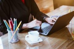 Bedrijfsvrouwenhanden die op het notitieboekjetoetsenbord bij de lijst in bureau typen Bedrijfs technologieconcept stock afbeeldingen