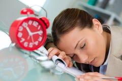 Bedrijfsvrouwenslaap bij bureau in het werk stock foto