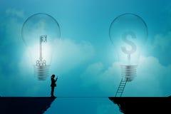 Bedrijfsvrouwentribune op een klip met sleutel en dollartekens in gloeilampen op een blauwe achtergrond, bedrijfsconcept Royalty-vrije Stock Fotografie