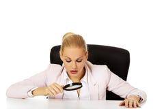 Bedrijfsvrouwenzitting achter het bureau en het onderzoeken van een vergrootglas Royalty-vrije Stock Afbeeldingen