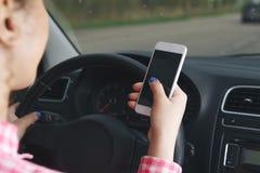 Bedrijfsvrouwenzitting in auto en het gebruiken van haar smartphone Modelbeeld met het vrouwelijke bestuurder en telefoonscherm stock foto