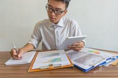 Bedrijfswerknemer die tablet gebruiken, schrijvend nota's stock foto