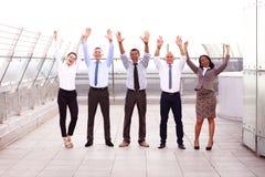 Bedrijfswinnaars De volledige lengte van groep gelukkige jongeren in het formele slijtage vieren, het houden bewapent opgeheven e stock fotografie